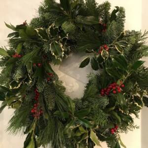 Traditional Christmas door wreath full of festive foliage and red berries